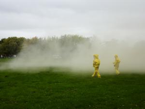 Two actors dressed in safety suits investigating a strange white mist.