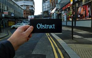 A hand with short nails holds up a small black card with the words 'Obstruct' on them. In the background is a Sheffield street scene with grey buildings either side of a road with double yellow lines on it. At the end of the adjoining street are old red brick buildings with scaffolding on them in a phase of redevelopment