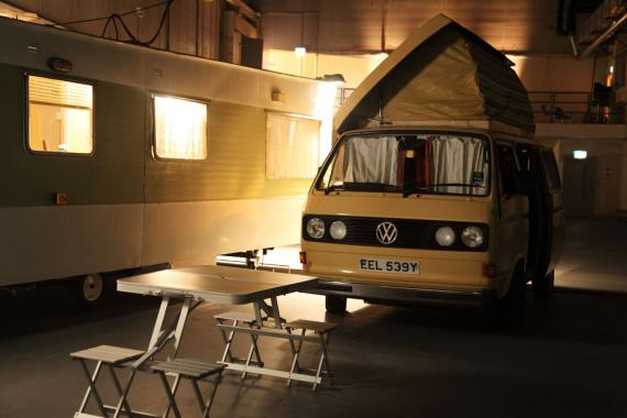 Two caravans installed in a darkened warehouse space. A picnic bench in the foreground.