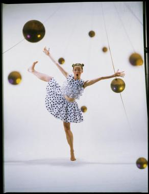 A girl in a polka-dot outfit dances amongst golden orbs.