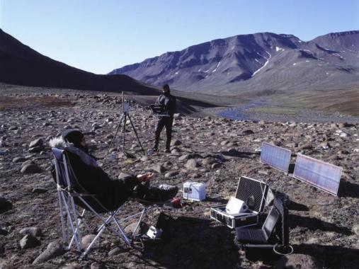 The artists stand in a large mountain range surrounded by electronic equipment and solar panels.