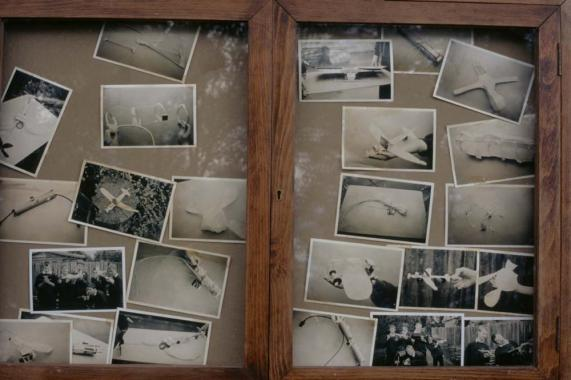 Photographs of handmade planes in a glass case.