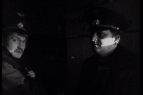 A black and white still showing two uniformed officers.