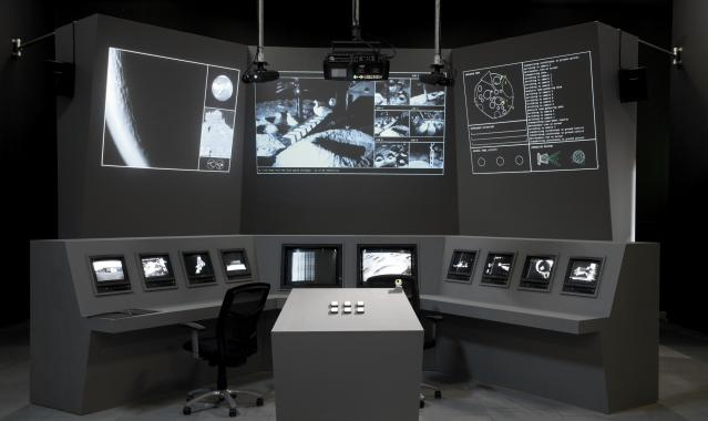 A futuristic-looking control panel. Screens display portraits of geese exploring a lunar landscape.