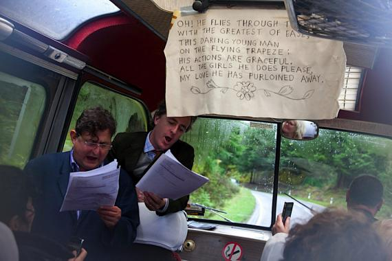 Adam Dant and Rob La Frenais sing at the front of a bus which is driving along a country road.