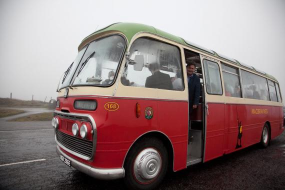 An old MacBraynes bus parked on a misty country road.