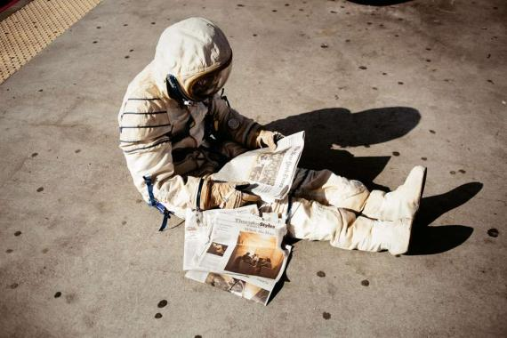An astronaut sits readinng a newspaper; The New York Times