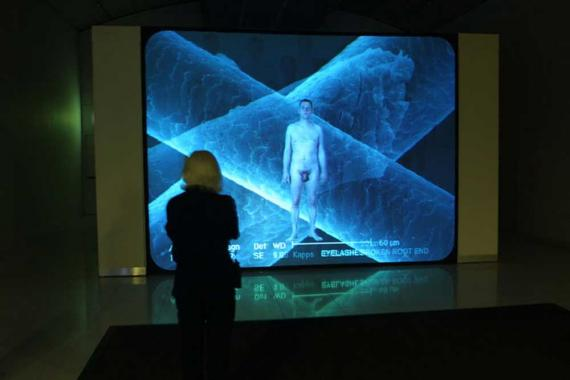 A woman watching a screen showing a nude male.