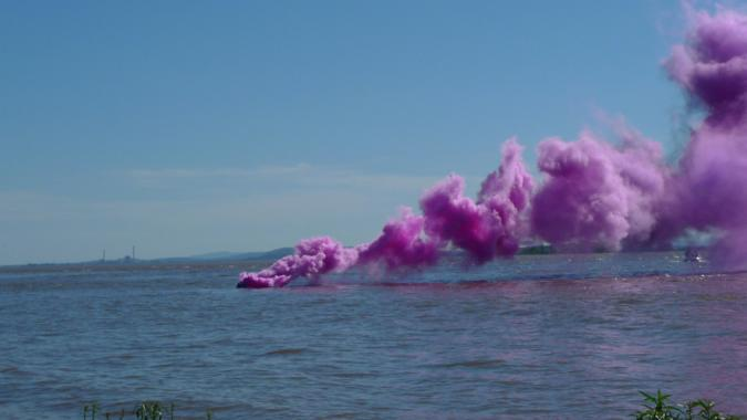 Violet smoke floats above a body of water.