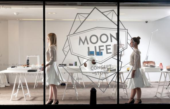 Two females dressed in white stand in the Moon Life Concept Store. The room is painted white and contains a table which holds many objects