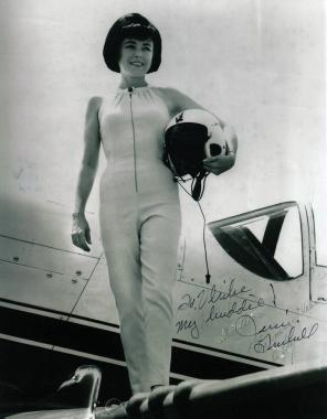 A glamourous woman stands atop a spacecraft dressed in a sixties-style astronautical suit.