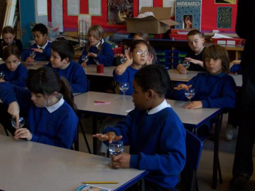 Pupils of Heathbrook school perform sound experiments with wine glasses half-filled with water.
